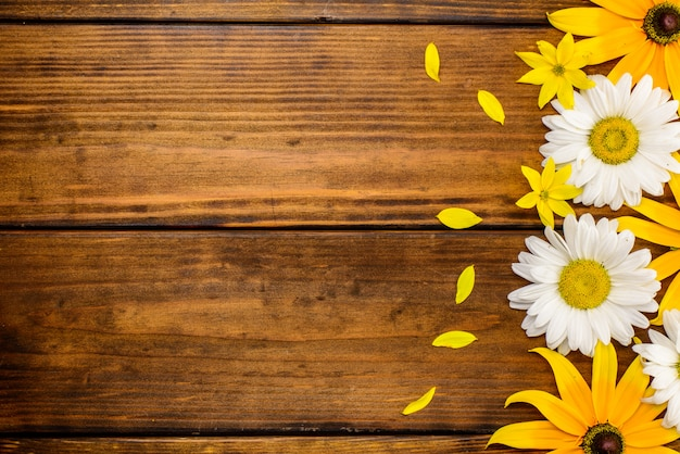 White daisies and garden flowers on a brown wooden table