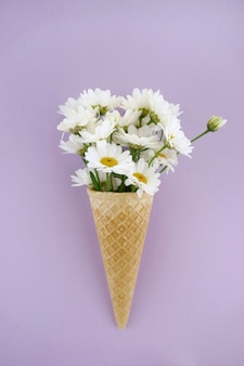 White daisies in a waffle cone on a light lilac background