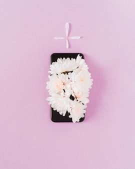 무덤의 모양을 만드는 검은 전화에 흰색 데이지 꽃. 개념적 최소한의 예술.