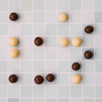 White and dark chocolate balls on checkered backdrop