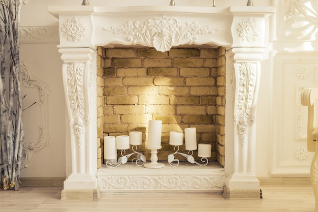 White decorative fireplace with candles in the room