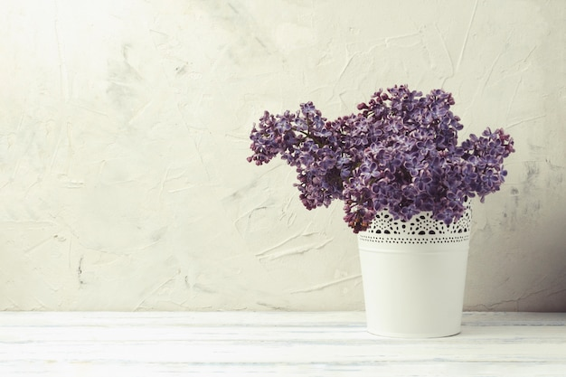 White decorative pail bucket with lilac on a white stone background and white wooden table.