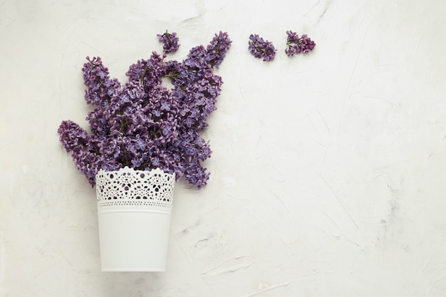 White decorative pail bucket with lilac on a white stone background.