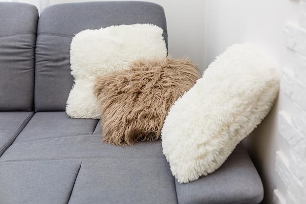 リビングルームのカジュアルなソファに白い装飾的な枕