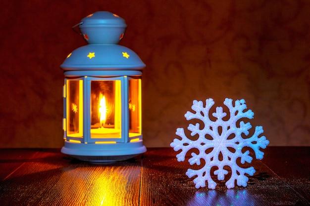 暗い背景にキャンドルとランタンの近くの白い装飾的な雪の結晶_