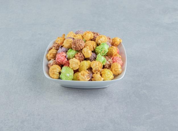 Un piatto fondo bianco di popcorn multicolori dolci.