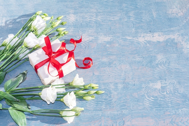 White delicate small roses and a white gift with a red ribbon on a blue wooden background, copy space, top view.
