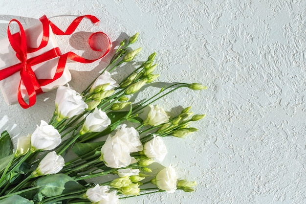White delicate small roses and a white gift with a red ribbon on a light plaster background, copy space, top view