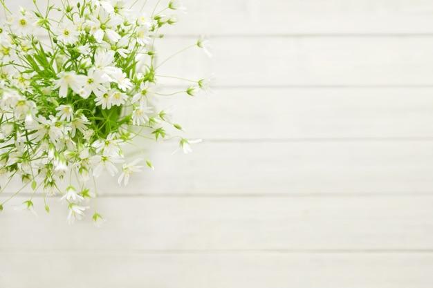 Белые нежные полевые цветы на деревянном фоне выборочной резкости вид сверху