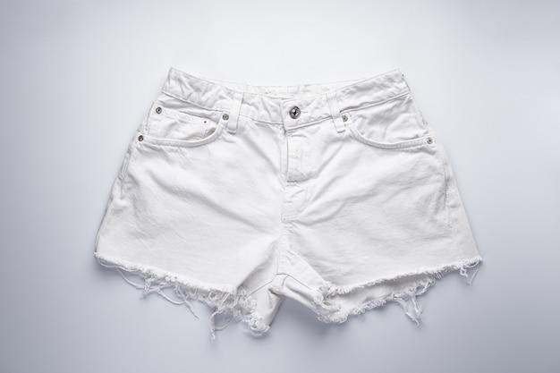 女性用ホワイトデニムショートパンツ、フロントポケット、トップビュー。