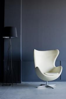 White designer chair in the interior of a black loft studio