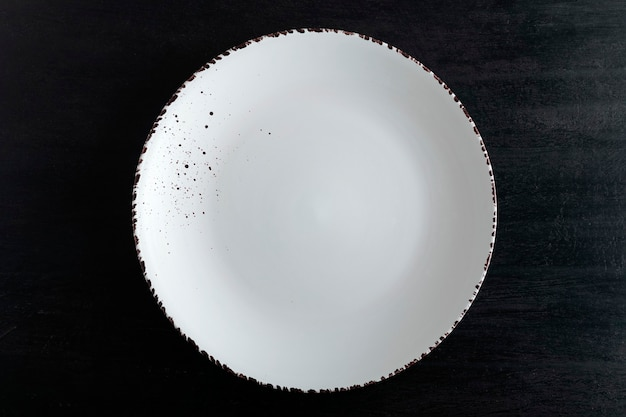 Белая дизайнерская тарелка на черном фоне, вид сверху. пустая тарелка