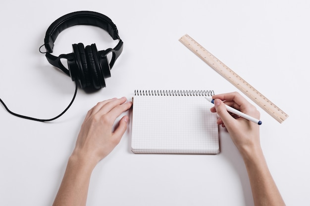 On a white desk are headphones, a ruler and a notebook, female hands writing pen