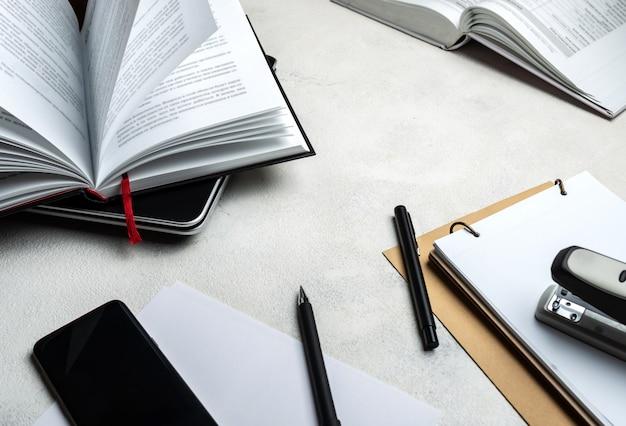Белый стол с ноутбуком, смартфон, книги, ручки, ноутбук. крупный план.