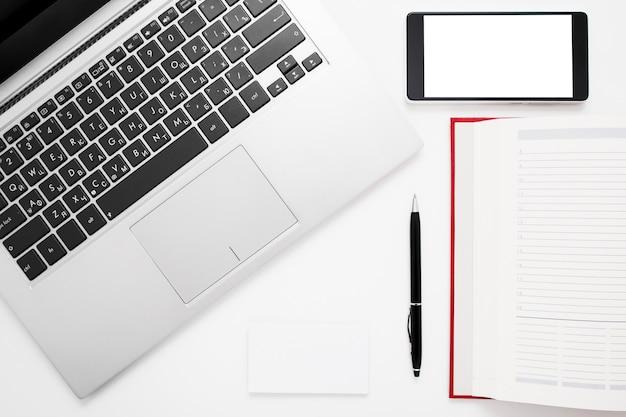 ノートパソコン、スマートフォン、ノートブックを備えた白い机