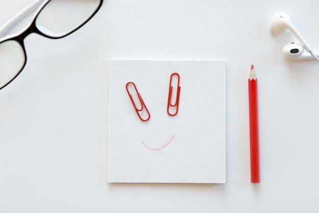 Белый стол с бумажным блоком, нарисованная улыбка на нем