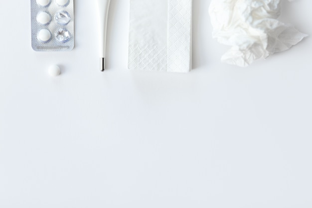 White desk with round pills, thermometer, paper crumpled napkin