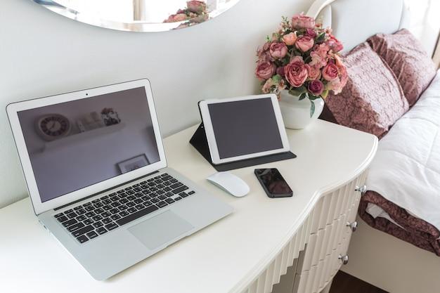 Белый рабочий стол с ноутбуком и таблетки
