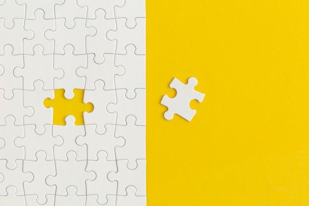 黄色の背景にパズルの白い詳細。ビジネス戦略、チームワーク。