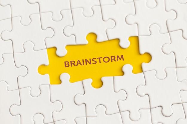 Белые детали головоломки с текстом мозгового штурма на желтом фоне