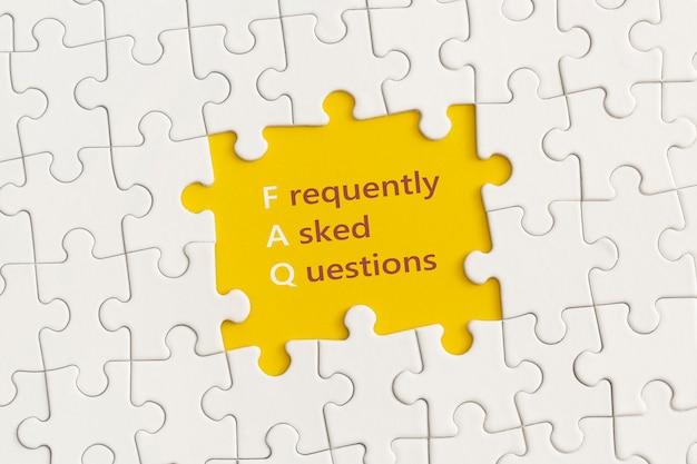 Белые детали головоломки с текстом faq на желтом фоне.