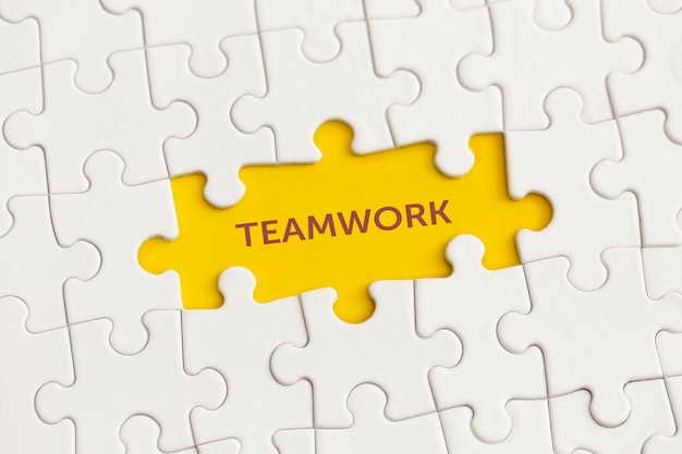 Белые детали головоломки с текстом «работа в команде» на желтом фоне.