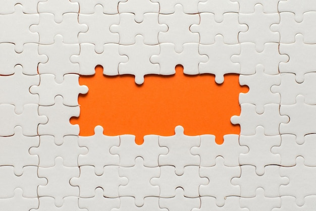White details of puzzle on orange and place for inscription.