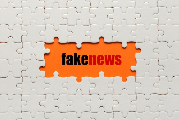 White details of puzzle on orange and word fake news