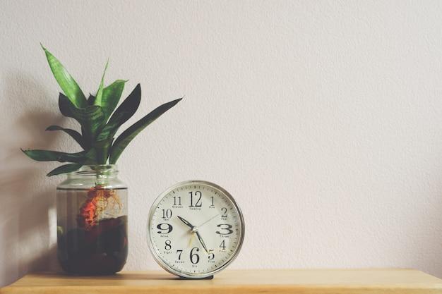 흰색 다이얼 테이블 알람 시계 또는 유리병에 식물이 있는 침대 옆 시계.