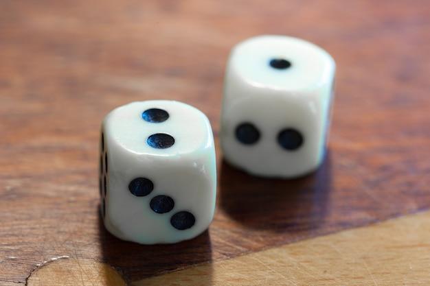 Белый кубик на деревянном. понятие удачи, случайности и досуга, числа 1 и 2.