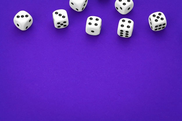 White dices against a purple background