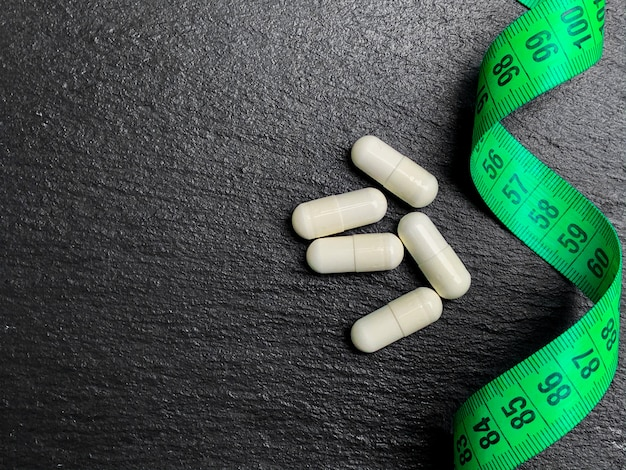 White diet pills next to a measuring tape