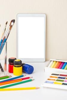 Белый цифровой планшет на белом столе с принадлежностями для рисования: кисти, акварель, мелки, маркеры, карандаш, акриловые краски. понятие о курсах рисования. скопируйте пространство. вертикальный