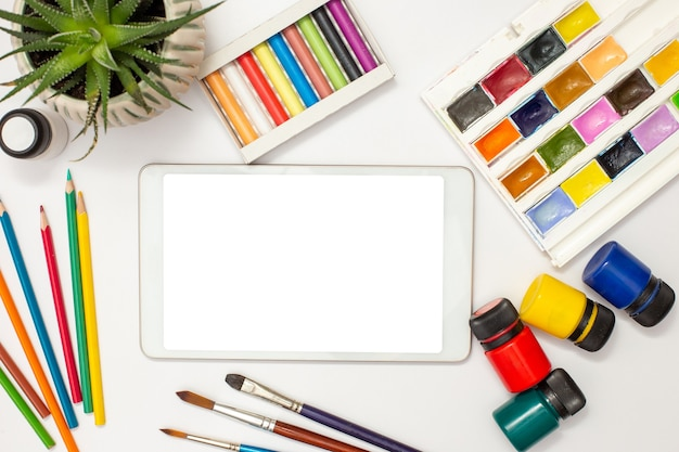 White digital tablet with a blank screen on a white table with drawing supplies: watercolors, pastel crayons, pencil, acrylic paints and succulent pot . copy space. mock up