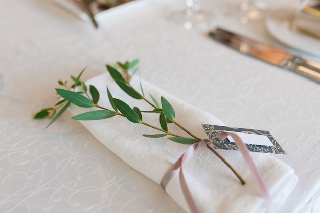 White dining napkin, tied with a dusty pink ribbon with branches of eucalyptus