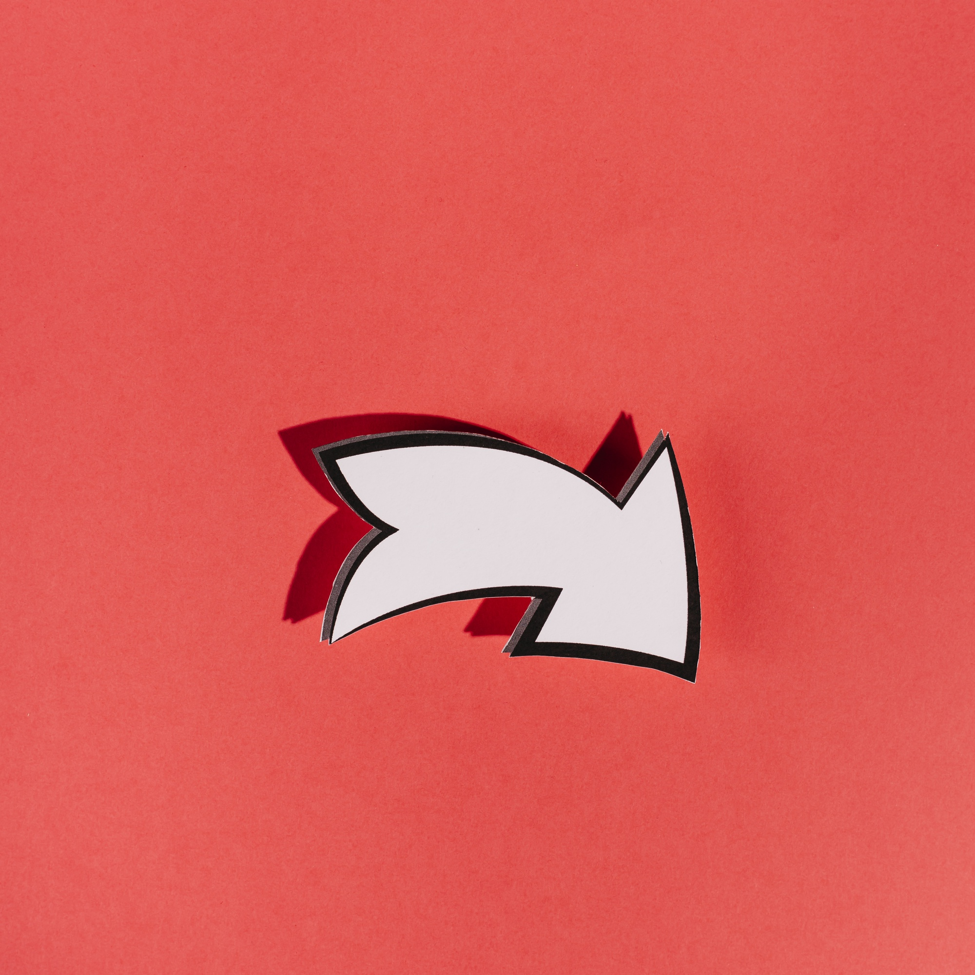 White directional arrow on red background
