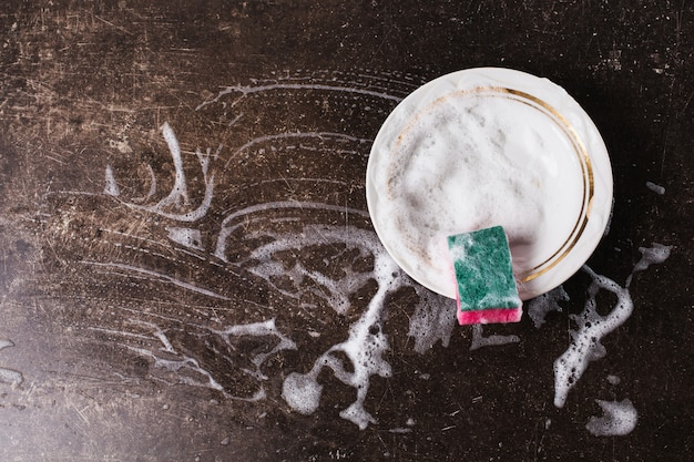 White dish, detergent and sponge for dishes on a dark marble background. hygiene. wash the dishes