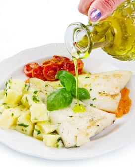 White dish of fresh black cod with potatoes and tomatoes sauce