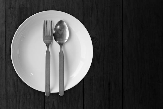 黒い木製の空白にフォークスプーンが付いた白い皿皿は、装飾用の食べ物の画像が空ではありません。