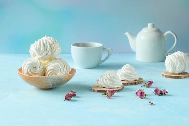 Белая посуда с белым зефиром с чашкой и чайником