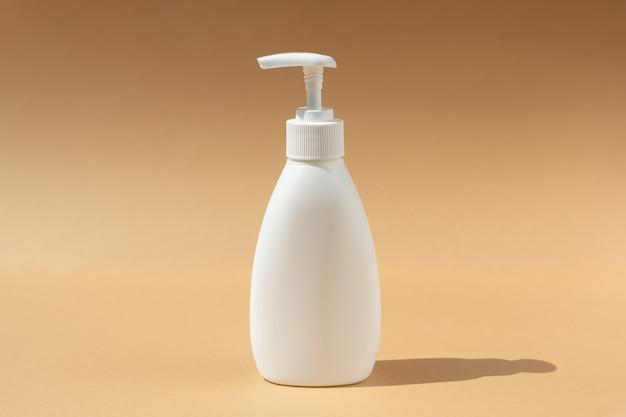 ベージュの背景にスパ化粧品用の白いディスペンサーボトル