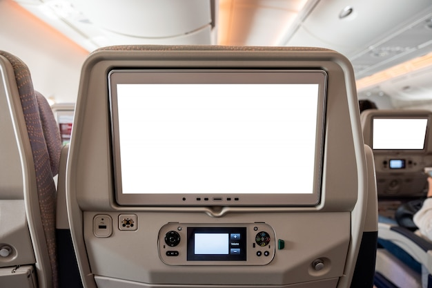 White display screen with joystick on rear seat in airplane