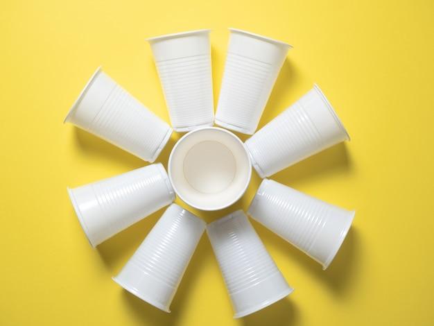 흰색 일회용 컵은 태양 모양으로 배치된 노란색 배경에 서 있습니다