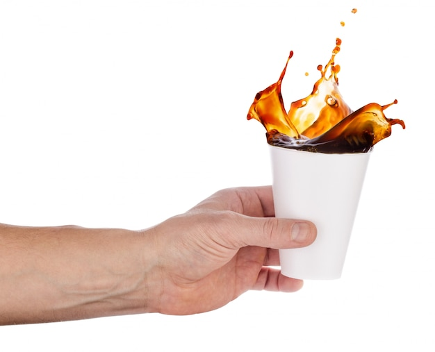 White disposable glass with splash of coffee in an outstretched hand