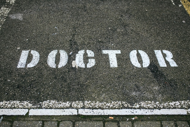 White doctor sign painted in a parking lot. reserved for doctors