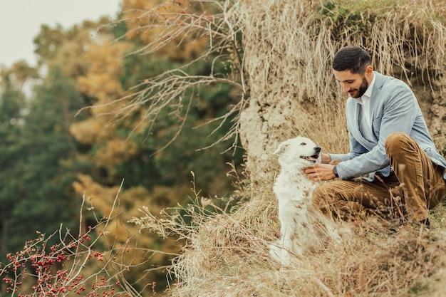 森の中で笑っている白い犬と若い男