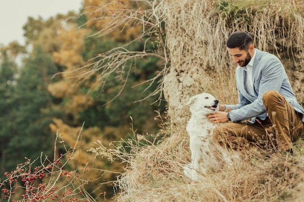 White dog and young man smiling in the forest