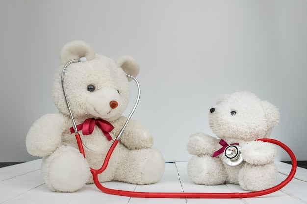 White doll bears with doctor instrument stethoscope on white.