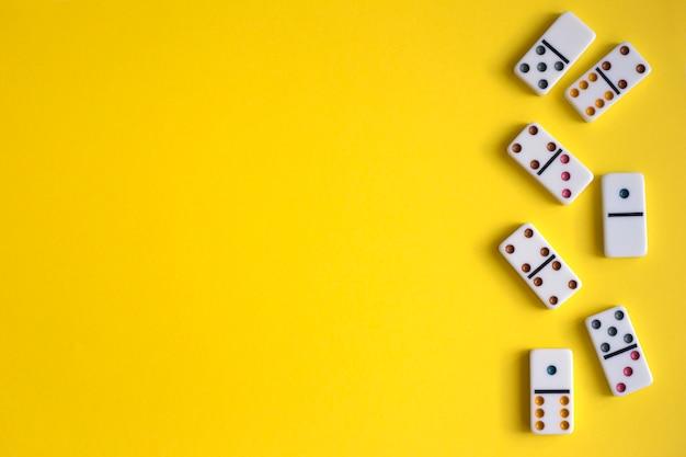 Белые домино на желтом фоне, вид сверху. настольная игра. место для текста