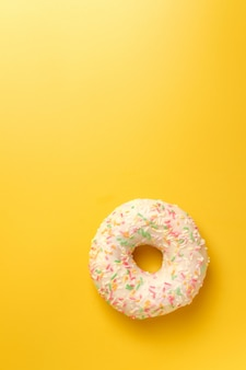 White donut on yellow background top view copy space